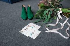 Sapatas nupciais verdes, ramalhete verde rico do casamento com fitas cor-de-rosa e um encontro elogioso do casamento em um assoal Fotos de Stock Royalty Free