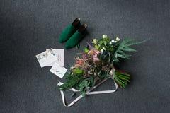 Sapatas nupciais verdes, ramalhete verde rico do casamento com fitas cor-de-rosa e um encontro elogioso do casamento em um assoal Foto de Stock Royalty Free