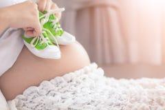 Sapatas pequenas para o beb? por nascer na barriga da mulher gravida Mulher gravida que guarda as sapatilhas pequenas do bebê que fotografia de stock royalty free