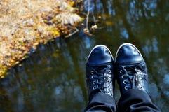 Sapatas pretas das sapatilhas contra a água, natureza foto de stock