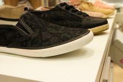 Sapatas pretas das sapatilhas na prateleira da loja Foto de Stock