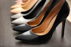 Sapatas pretas elegantes na prateleira de madeira, Foto de Stock Royalty Free