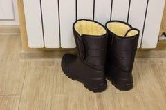 Sapatas pretas molhadas do inverno perto de um radiador de aquecimento, secagem da sapata, foto do close-up imagens de stock royalty free