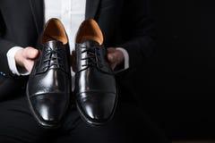 Sapatas pretas na mão do homem de negócios Imagens de Stock