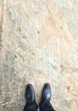 Sapatas pretas no concreto Fotografia de Stock Royalty Free