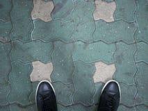 Sapatas pretas no fundo do bloco de cimento Fotografia de Stock Royalty Free
