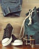 Sapatas, trouxa, calças de brim e binóculos Imagem de Stock
