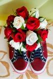Sapatas vermelhas em um assoalho marrom com o ramalhete das rosas Fotos de Stock Royalty Free