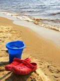 Sapatas vermelhas verticais na praia fotografia de stock