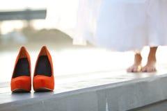 sapatas Vermelho-alaranjadas do casamento na frente da noiva descalça foto de stock