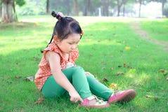 Sapatas vestindo da menina no gramado Fotos de Stock Royalty Free