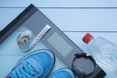Sapatilhas azuis, água, escala digital no fundo azul imagem de stock royalty free