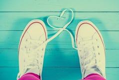 Sapatilhas brancas com coração no fundo de madeira azul, filtrado Fotos de Stock