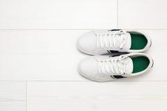Sapatilhas brancas no assoalho de madeira branco Foto de Stock Royalty Free