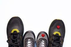 Sapatilhas cinzentas da criança com poucos coração e pares vermelhos de sapatilhas adultas pretas imagem de stock