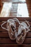 Sapatilhas cinzentas do bebê no fundo de madeira Imagem de Stock