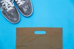 Sapatilhas cinzentas em um fundo azul fotos de stock