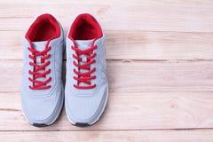 Sapatilhas cinzentas que correm com laços vermelhos em um fundo de madeira imagem de stock royalty free