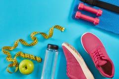 Sapatilhas com a fita de medição no fundo azul ciano Centímetro na cor amarela, nas sapatilhas cor-de-rosa, nos pesos e na garraf fotografia de stock