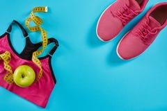 Sapatilhas com a fita de medição no fundo azul ciano Centímetro na cor amarela, sapatilhas cor-de-rosa, parte superior fêmea do e fotografia de stock royalty free