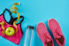 Sapatilhas com a fita de medição no fundo azul ciano Centímetro na cor amarela, sapatilhas cor-de-rosa, parte superior fêmea do e imagens de stock royalty free