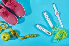 Sapatilhas com a fita de medição no fundo azul ciano Ostente sapatas e o equipamento desportivo para a forma saudável fotos de stock