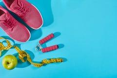Sapatilhas com a fita de medição no fundo azul ciano Ostente sapatas e o equipamento desportivo para a forma saudável fotografia de stock