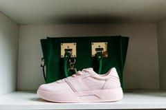 Sapatilhas cor-de-rosa com solas grossas e um saco verde no fundo na prateleira branca da loja fotos de stock royalty free