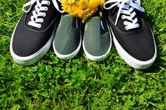 Sapatilhas da criança e sapatilhas adultas na grama fotografia de stock