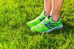 Sapatilhas das sapatas dos esportes em um campo de grama verde fresco fotografia de stock