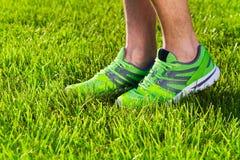 Sapatilhas das sapatas dos esportes em um campo de grama verde fresco foto de stock
