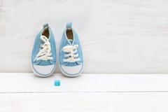 Sapatilhas do ` s das crianças no azul e em um cubo com um número um Fotografia de Stock