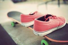 Sapatilhas e skate no skatepark Fotografia de Stock