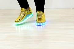 Sapatilhas elegantes com iluminação do diodo emissor de luz nos pés de uma menina imagem de stock royalty free