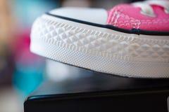 Sapatilhas elegantes cor-de-rosa do close up na prateleira da loja Foto de Stock Royalty Free