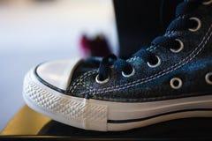Sapatilhas elegantes do close up na prateleira da loja Foto de Stock