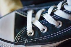 Sapatilhas elegantes do close up na prateleira da loja Imagem de Stock