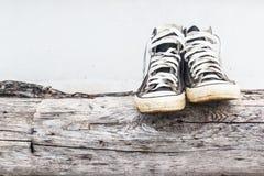Sapatilhas pretas nos muros de cimento de madeira e cinzentos velhos do registro Imagens de Stock