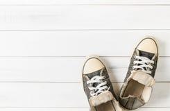 Sapatilhas pretas velhas na madeira fotos de stock royalty free