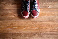 Sapatilhas vermelhas do casamento no assoalho marrom Imagem de Stock
