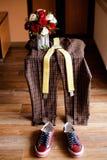 Sapatilhas vermelhas, roupa, rosas da noiva na cadeira Fotografia de Stock