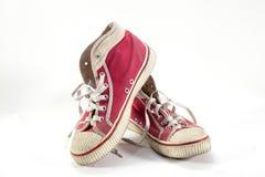 Sapatilhas vermelhas velhas no fundo branco. Imagens de Stock