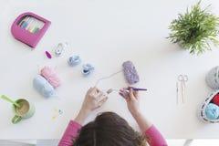 Sapatinhos de lã de confecção de malhas da mulher para um bebê em seu estúdio Foto de Stock