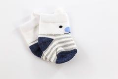 Sapatinhos de lã do bebê branco e azul para o rapaz pequeno isolado no fundo branco Fotos de Stock