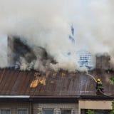 Sapeur-pompier au travail avec de l'eau sur s'éteindre le feu Image libre de droits