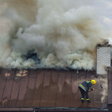 Sapeur-pompier au travail avec la hache sur s'éteindre le feu Photographie stock libre de droits