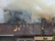 Sapeur-pompier au travail sur s'éteindre le feu sur le toit Photographie stock libre de droits
