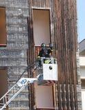 Sapeur-pompier dans le panier des pompes à incendie d'ouvrier chargé des pompes Photo stock