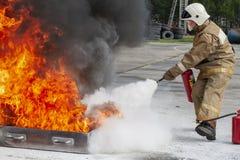 Sapeur-pompier pendant la formation avec un feu énorme dans le brasero photographie stock