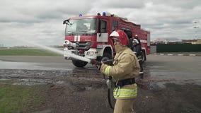 Sapeur-pompier tenant le tuyau de l'eau pr?s du camion avec l'?quipement banque de vidéos